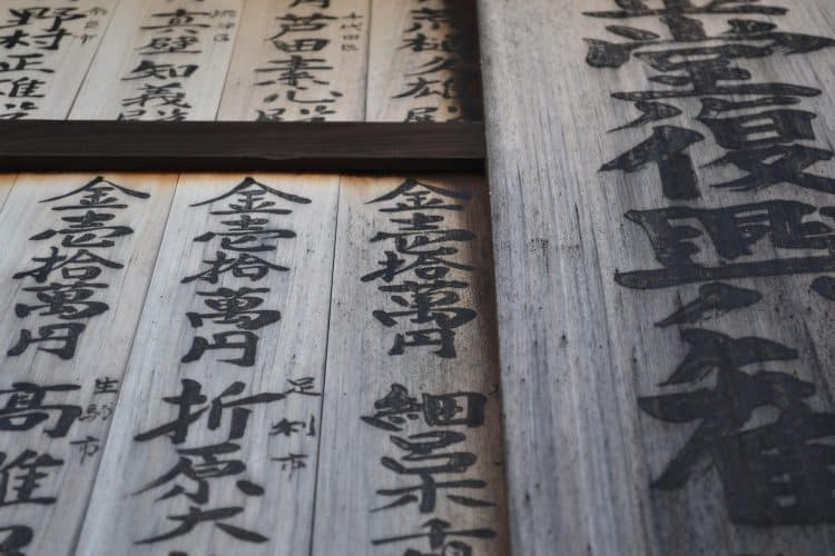 Japanese kanji characters on wood panels at a temple or shrine