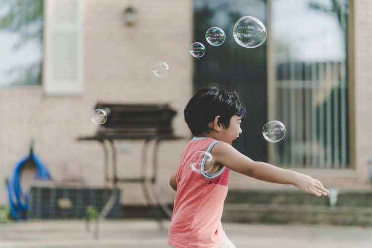 A Japanese boy blowing bubbles. Create your own language bubble to create an effective immersion environment for faster language learning!