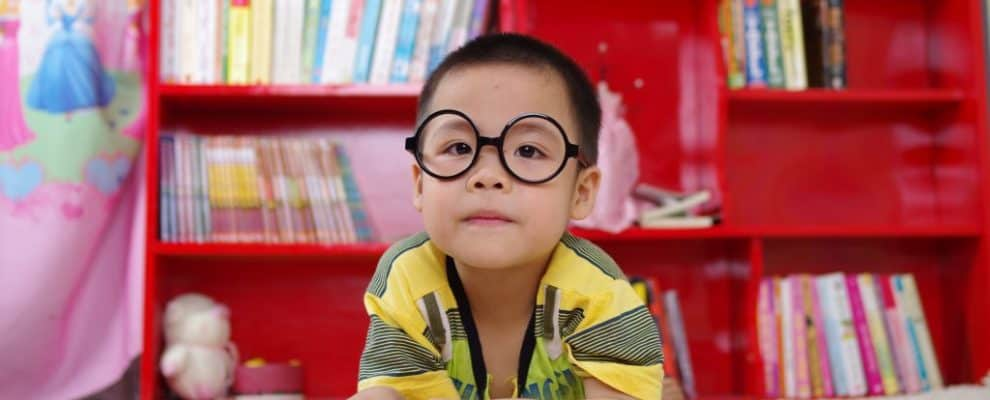 Boy with glasses studying Japanese kanji symbols from books