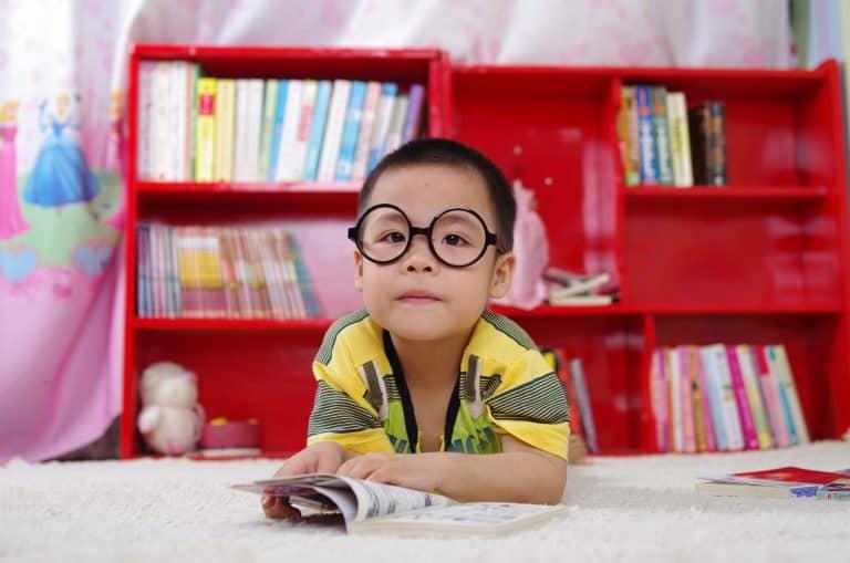Boy with glasses studying Japanese kanji symbols from books