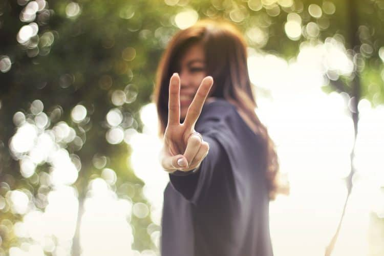girl doing the peace sign: learn how to say i am learning japanese in japanese, and other useful phrases, to start having great conversations in Japanese!