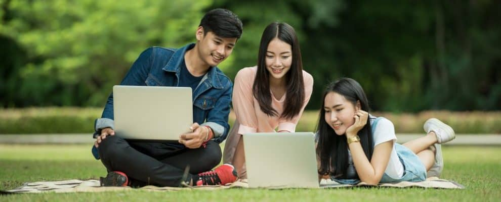 best websites for learning Japanese - students learning Japanese outside online on the grass