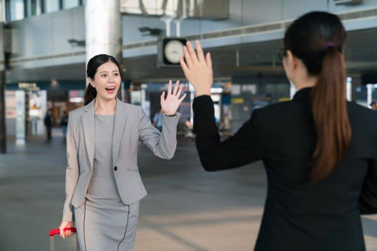 how to say hello in japanese formal - two coworkers greeting at airport