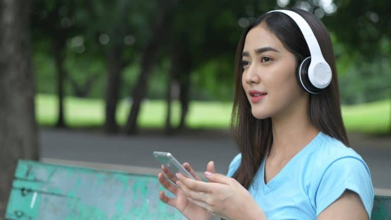 An Asian girl sits on a park bench listening to a language course on headphones