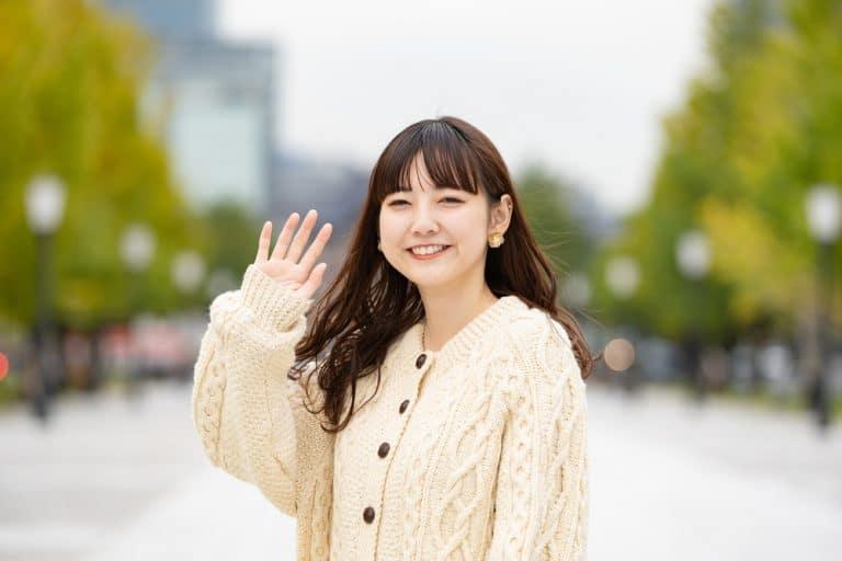 A young Japanese woman waving goodbye