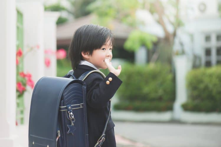 A young Japanese boy in school uniform and backpack waves goodbye