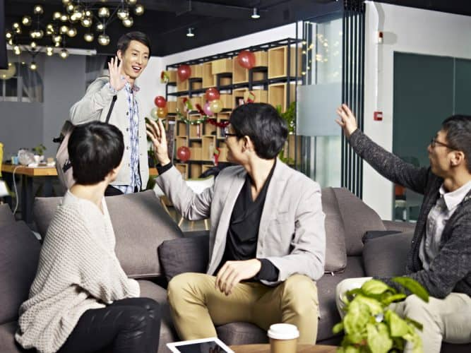 Saying goodbye to coworkers in Japanese: three professional young Japanese men sit on a sofa in a bar, waving goodbye to another man who is leaving.