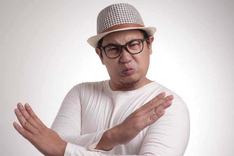Funny Japanese man in glasses and hat crossing his arms in a 'no' gesture