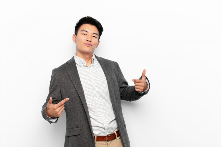 young asian man in suit looking arrogant and pointing at himself