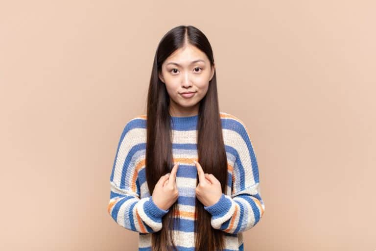 young japanese woman pointing to self with a quizzical look