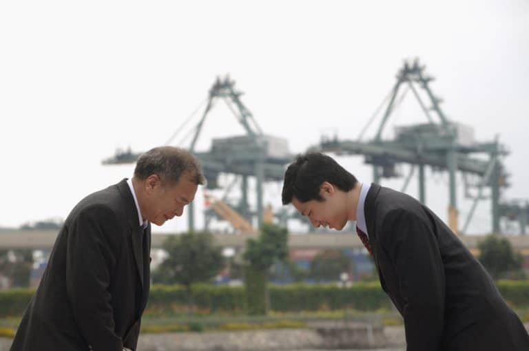 two Japanese businessmen bowing to each other