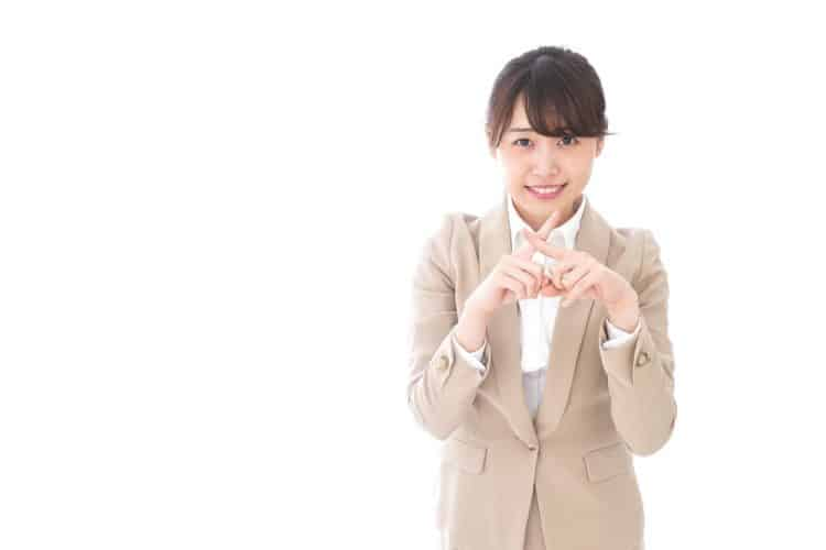 A cute young Japanese woman in a beige suit makes an x with her fingers in a gesture meaning 'no'