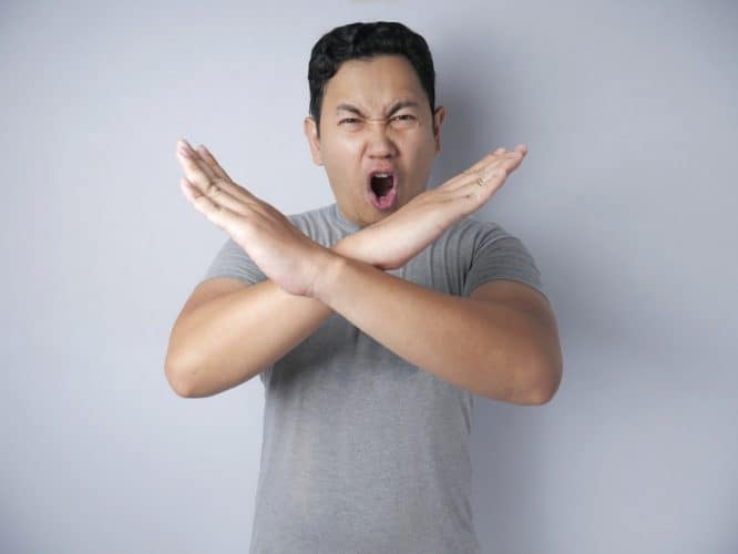 Young Japanese man shouting no and crossing his arms