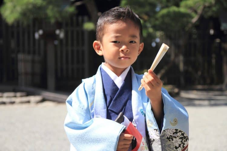 A young Japanese boy wearing traditional clothing, including a haori jacket, for his Seven-Five-Three birthday ceremony.