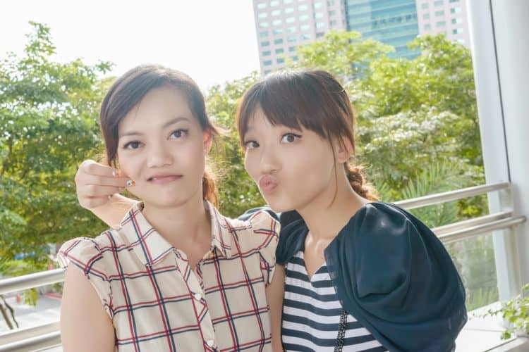 Two young Asian women with their arms round each other, pulling silly faces