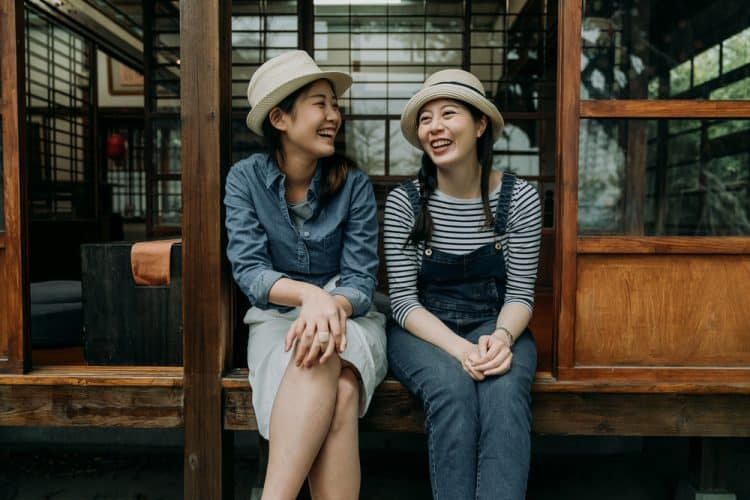 Two young Japanese women sit on the porch of a traditional Japanese home, chatting