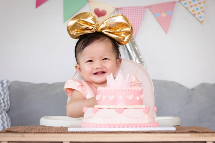 Cute, smiling Asian baby girl celebrating her first birthday with a pink princess cake and a big gold bow on her head.