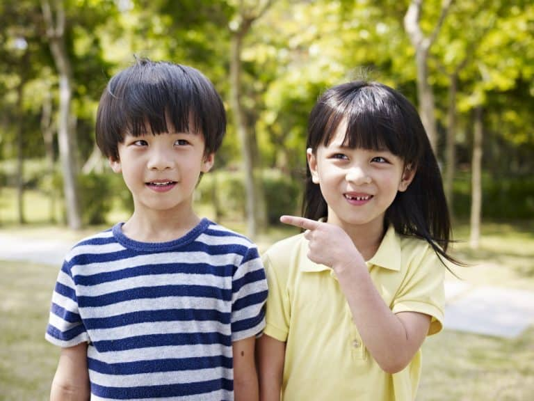 you in japanese: a cute japanese boy and girl, about eight years old, smile and point at each other.