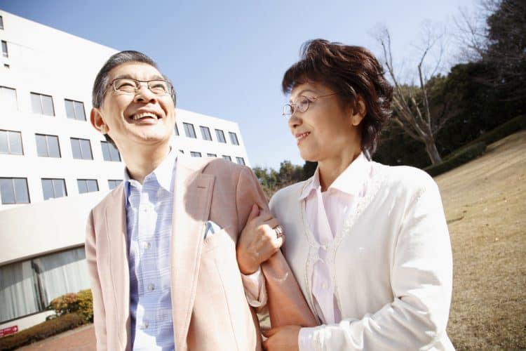 An older Japanese couple walk with linked arms. The woman is looking at her husband lovingly.
